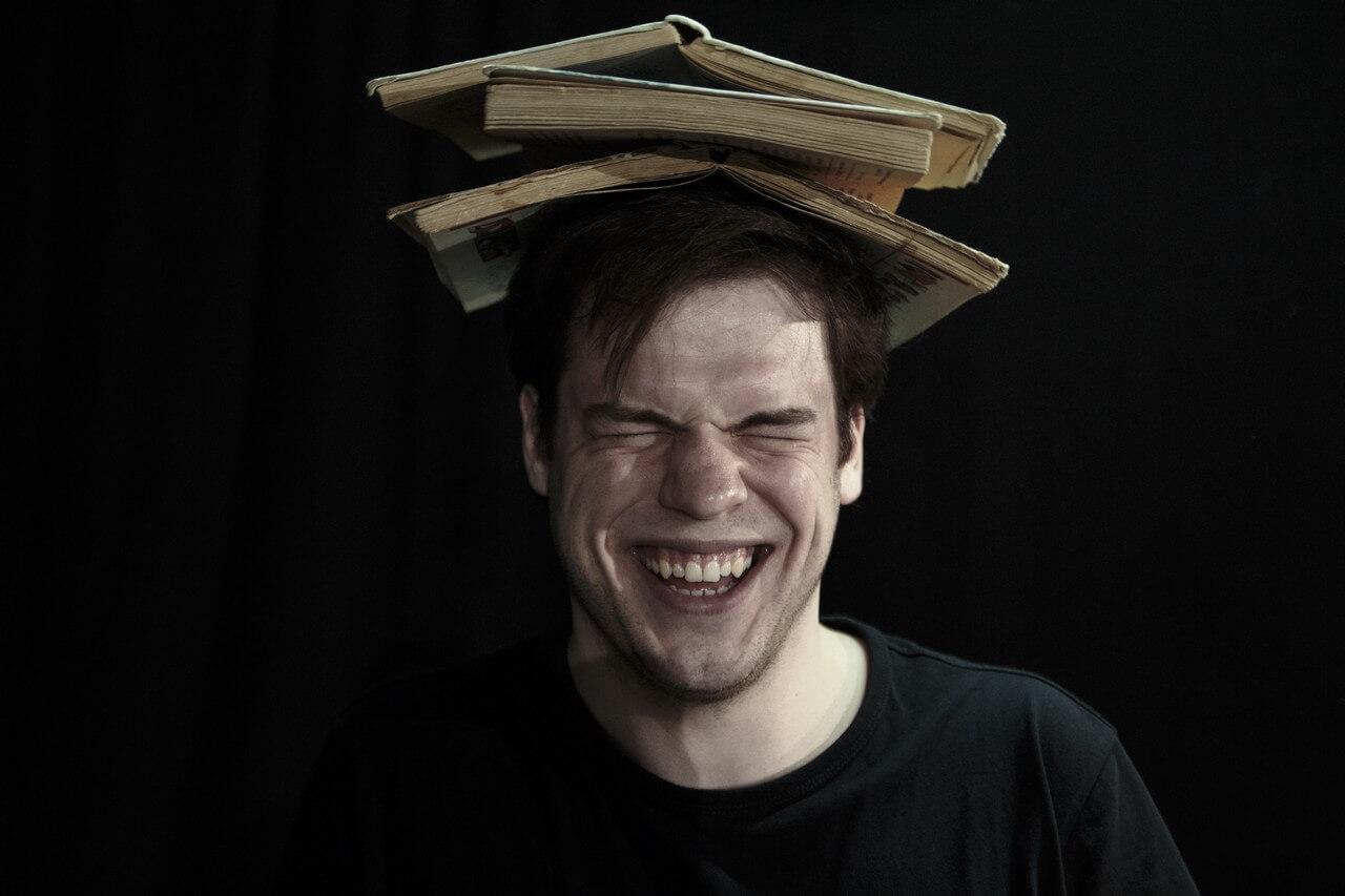 Zdecie ze spektaklu Bajka o księciu Pipo. Przedstawia aktora o szeroko usmiechnietej twarzy, zamknietymi oczami. Na głowie ma trzy rozłożone książki.