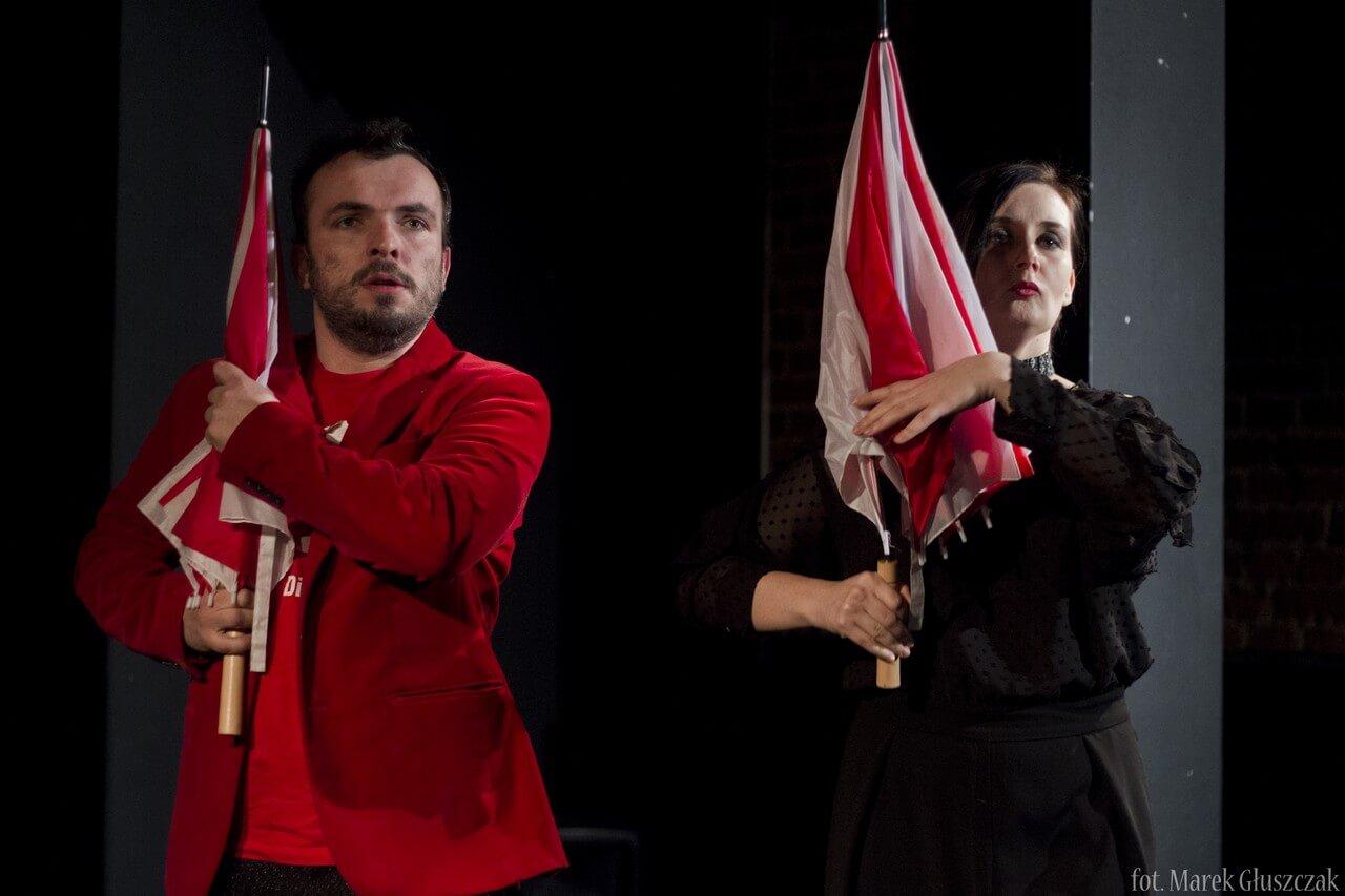 Zdjecie do spektaklu Burmistrz. na zdjęciu dwoje aktorów trzymających na ramieniu czarnobiałe parasolki imitująjące karabiny. Aktor ubrany na czerwono, aktorka na czarno.