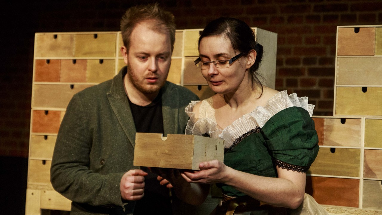 Zdjęcie ze spektaklu Bajka o księciu Pipo. Pokazuje dwoje aktorów zaglądających do drewnianej skrzyneczki.