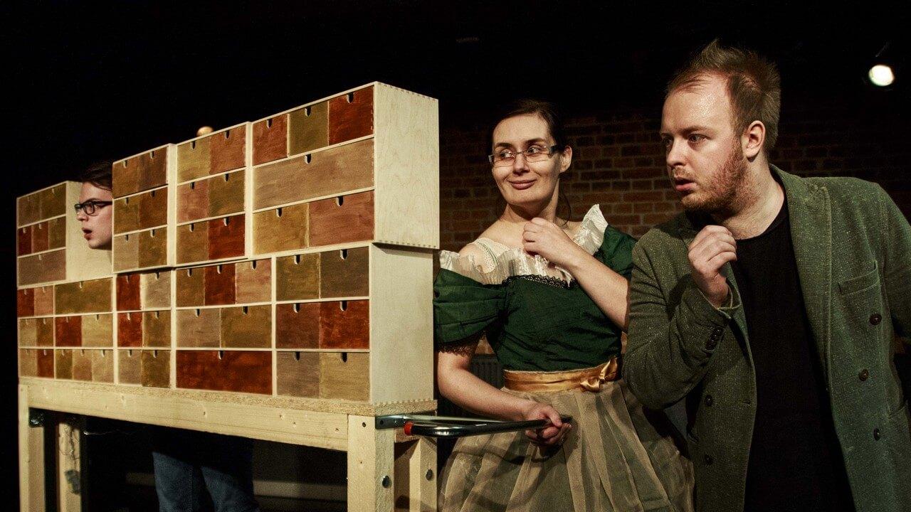 Zdjęcie ze spektaklu Bajka o księciu Pipo. Dwoje aktorów przy konstrukcji złożenej z małych szuflad. Aktor jest zdziwiony, aktorką sie uśmiecha.