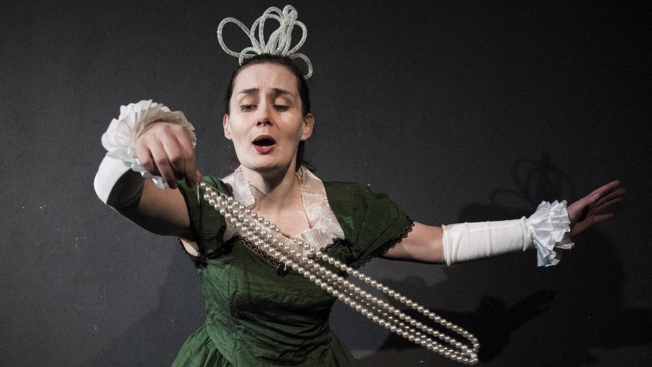 Zdjęcie ze spektaklu Bajka o księciu Pipo. Przedstawia aktorke przebraną w zieloną suknię w stylu królowej. Na głowie ozdoba w stylu korony. W reku sznur pereł.