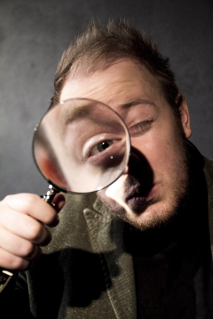 Zdjęcie ze spektaklu Bajka o księciu Pipo. Pokazuje aktora na duzym zbliżeniu patrzącego cenralnie prze lupę. Lupa poiększa mu oko.