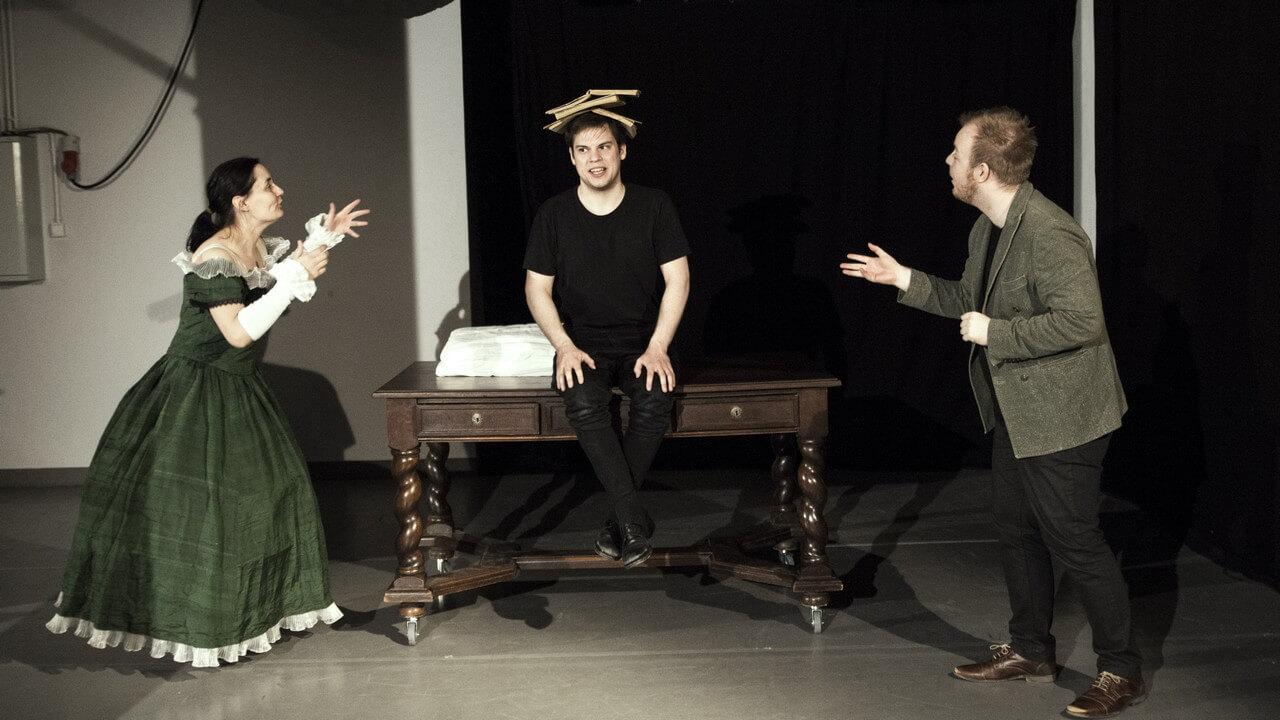 Zdjęcie ze spektaklu Bajka o księciu Pipo. Przedstawia trójke aktorów. Mężczyzna siedzi centralnie na stole z 3 ksiażkami na głowie. Aktorka po lewej stronie w obszernej zielonej sukni. Z prawej aktor w szarej marynarce.