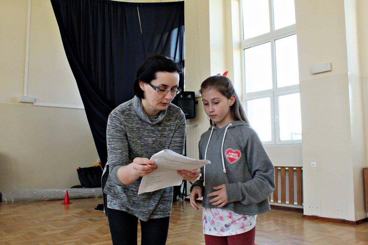 Próby do spektaklu Była sobie szkoła - reżyserka trzyma scenariusz, tłumaczy cos dziewczynce stojącej obok.