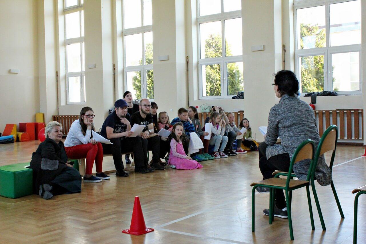 Próby do spektaklu Była sobie szkoła - reżyserka siedzi na krzesełku i rozmawia z obsadą (dzieci i rodzice) siedzącą na przeciwko niej.
