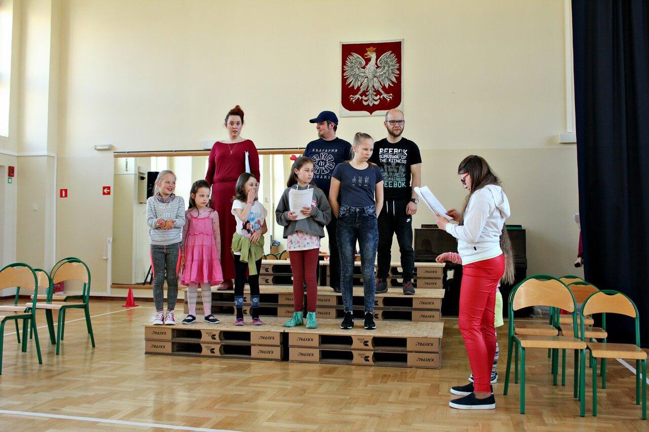Próby do spektaklu Była sobie szkoła. Aktorzy stoja na podwyższeniu zrobionym z europalet. Dzieci niżej, rodzice wyżej. Po prawo dziewczynka w czerwonych spodniach trzyma scenariusz.