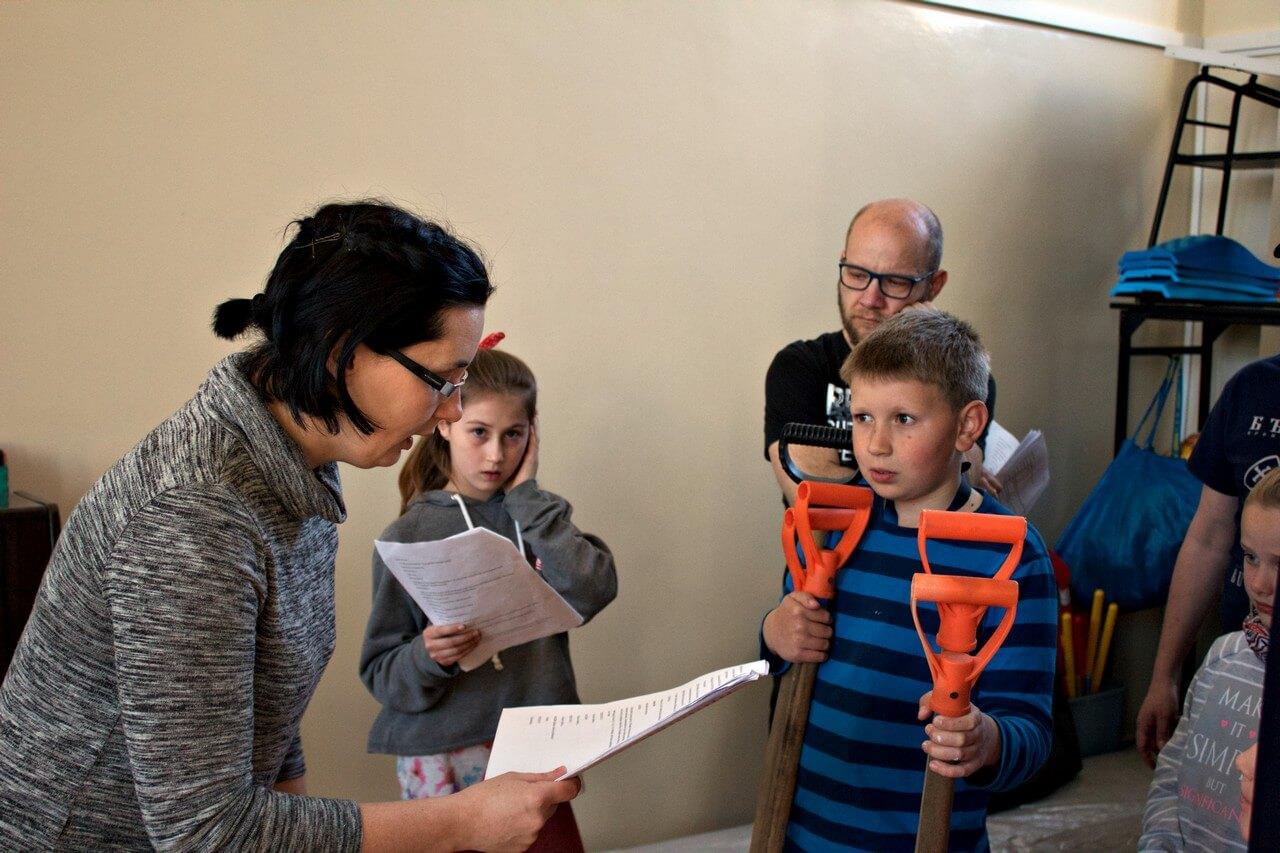 Próby do spektaklu Była sobie szkoła - reżyserka trzyma tekst, obok chłopiec trzynający w rekach łopaty.