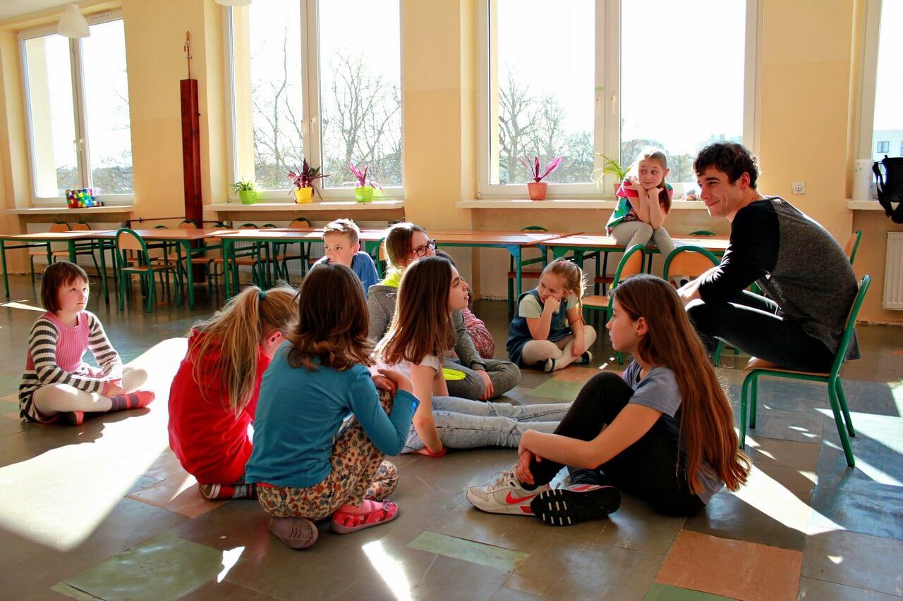 Na zdjęciu grupa dzieci siedzących w okregu na podłodze i słuchających instruktora.