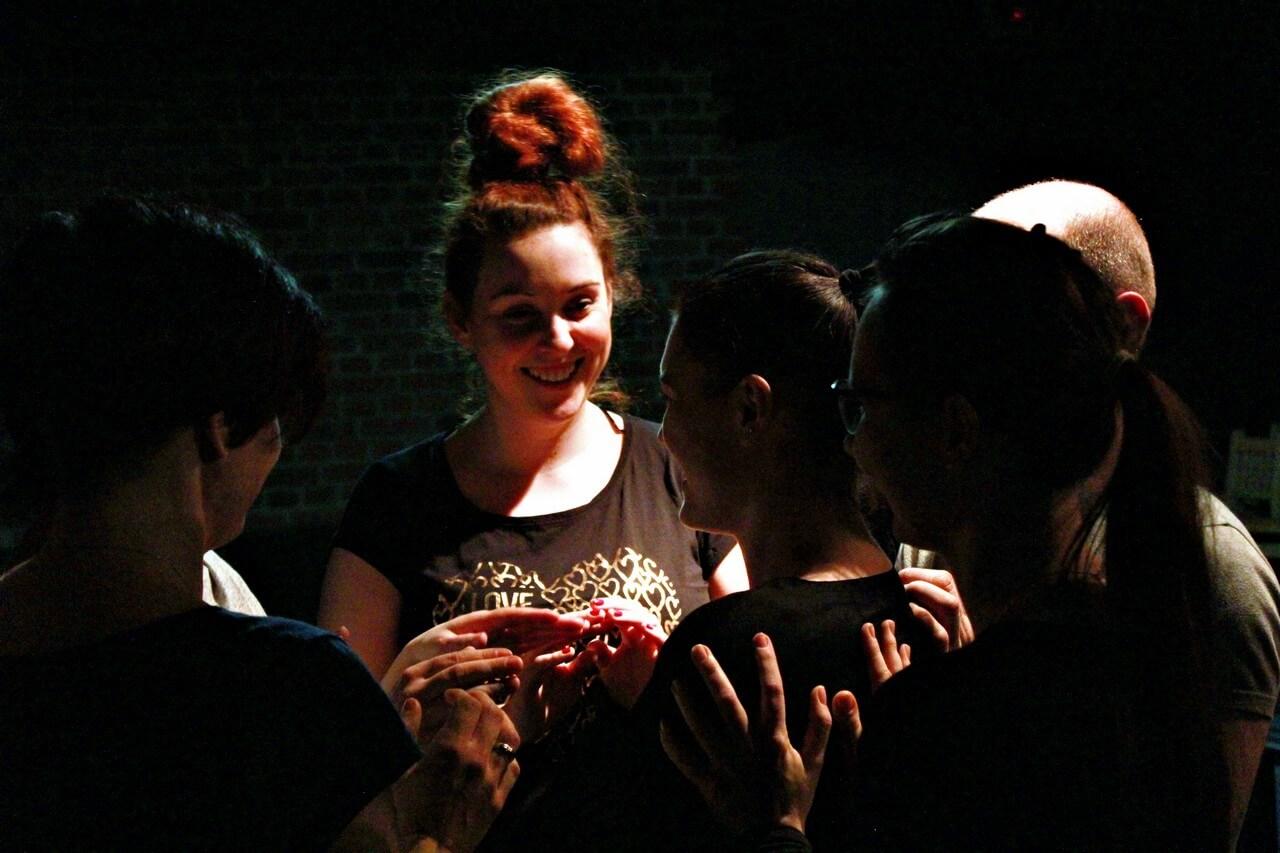 na zdjeciu usmiechnieta kobieta o rudych włosach spietych w kok. w otoczeniu innych ludzi.