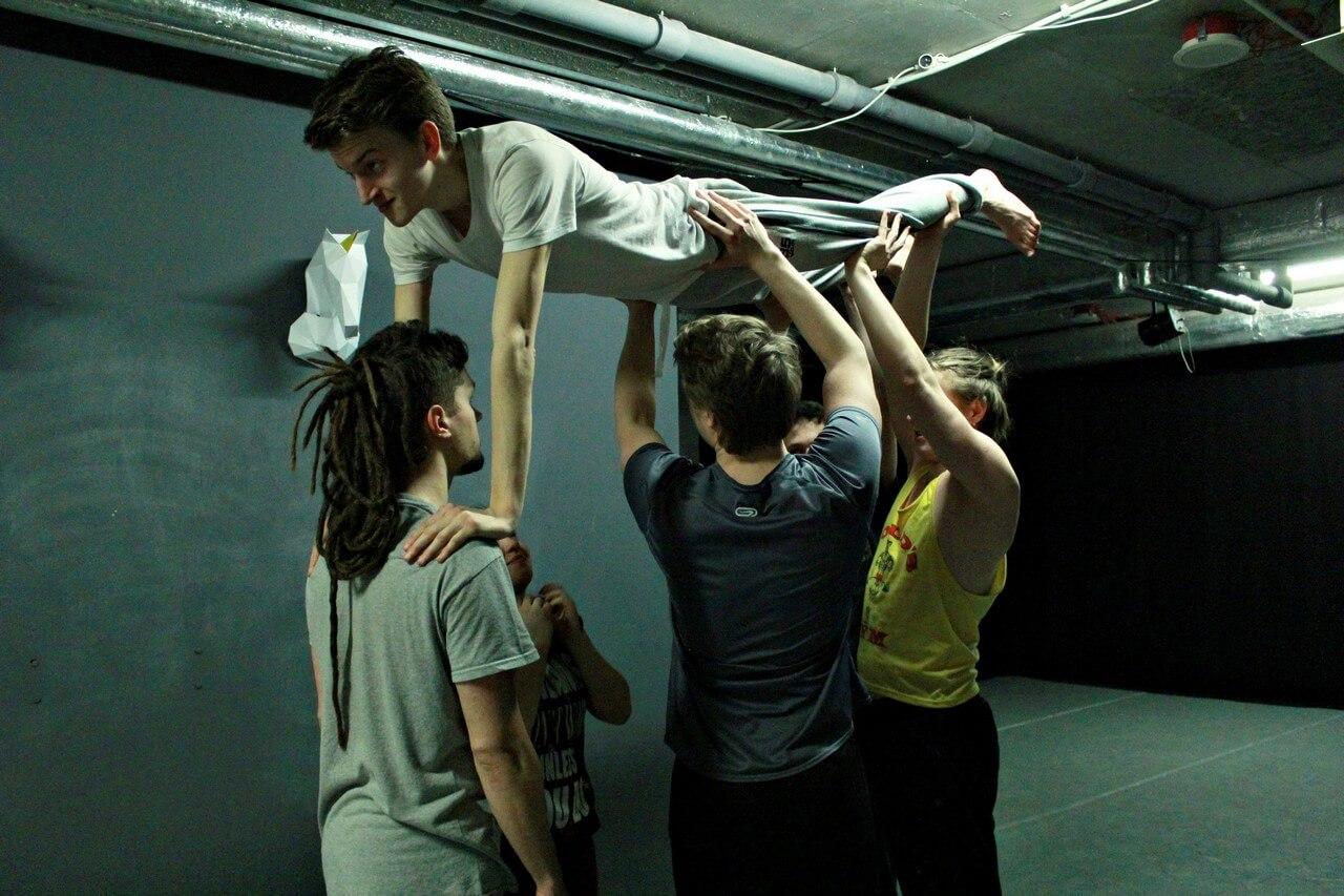 Trójka młodych ludzi trzyma w górze leżacego chłopaka.