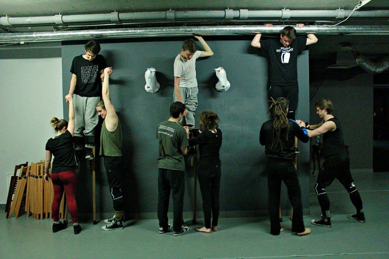 Na zdjęciu trzy osoby stoja pod sścianą na szczudłach. Kolejne sześć im pomaga ustać.