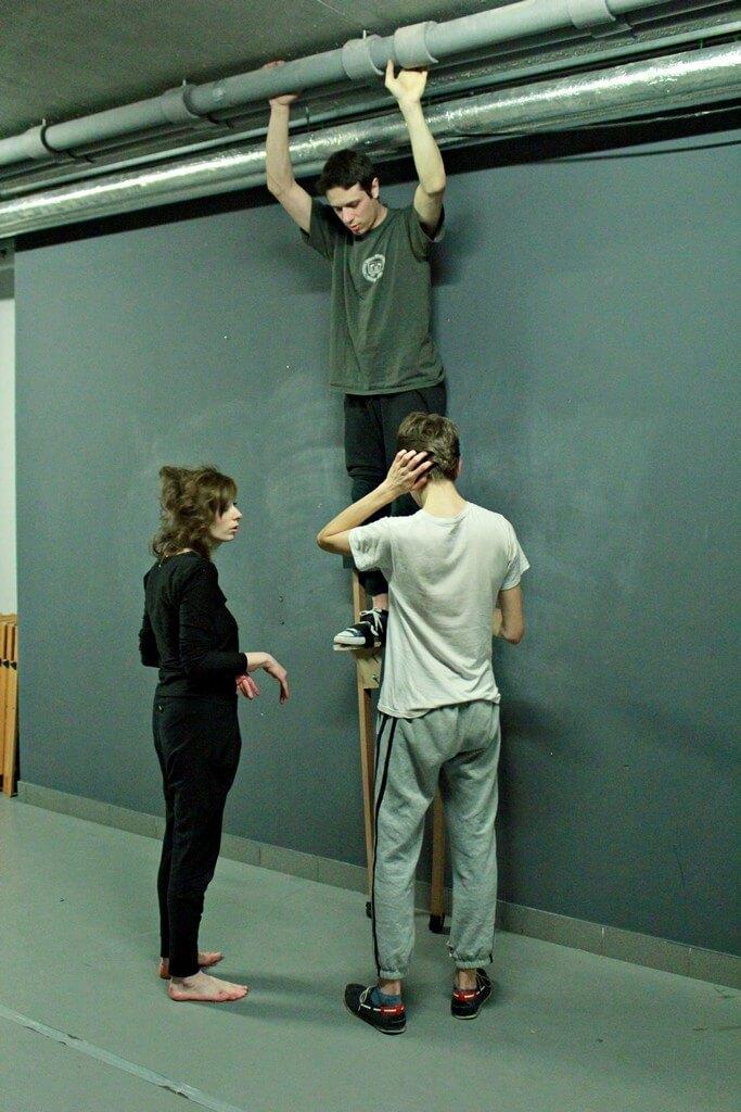 Mężczyzna stoi na szczudłach. Kobieta i mężcyzna mu pomagają.