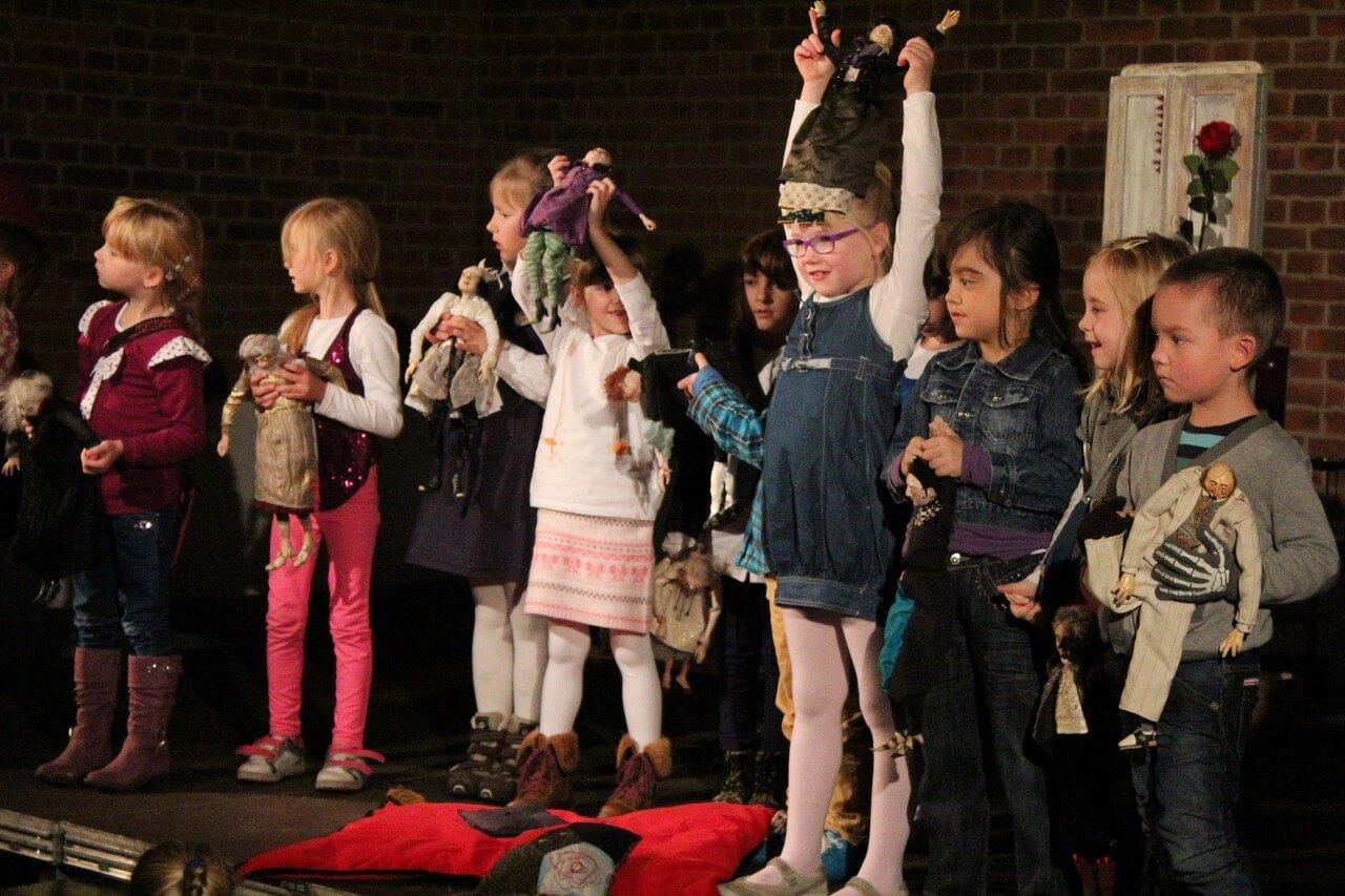 Zdjęcie przedstawia grupę dzieci stojących w rzędzie i trzymających lalki ze spektaklu śpiaca królewna.