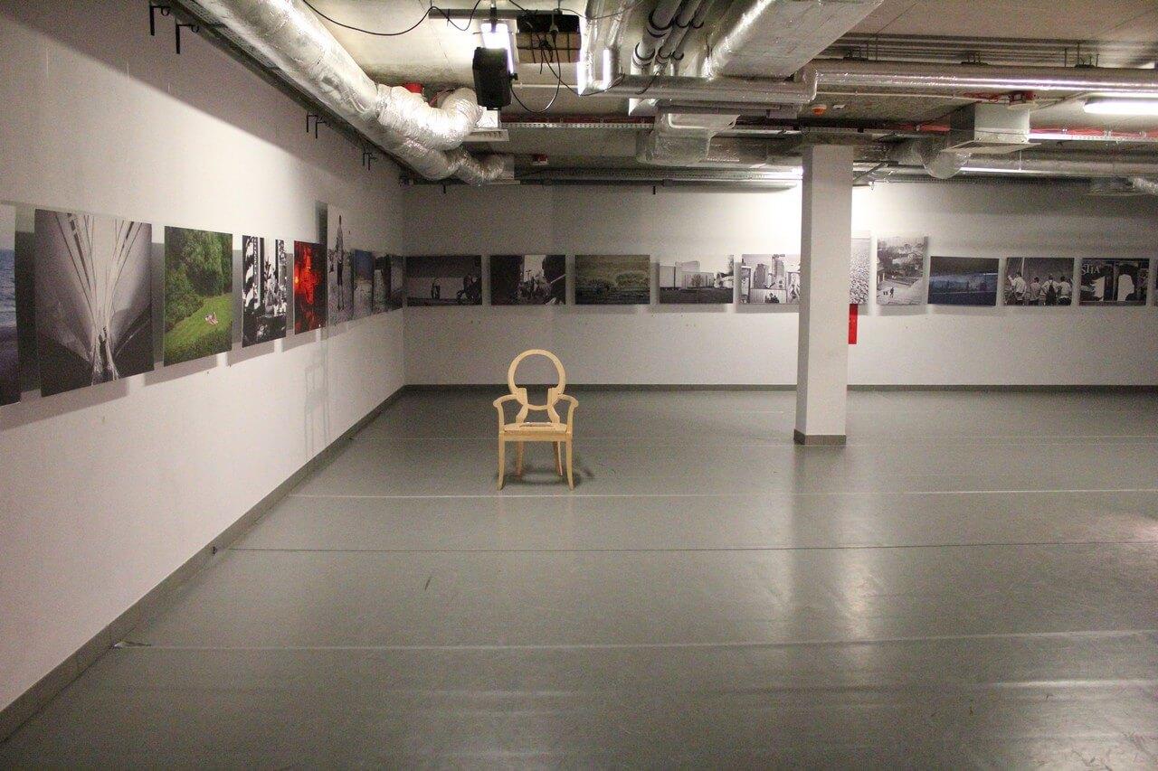 Szara sala teatralna. Na ścianach rząd obrazów. Po srodku stoi tron.