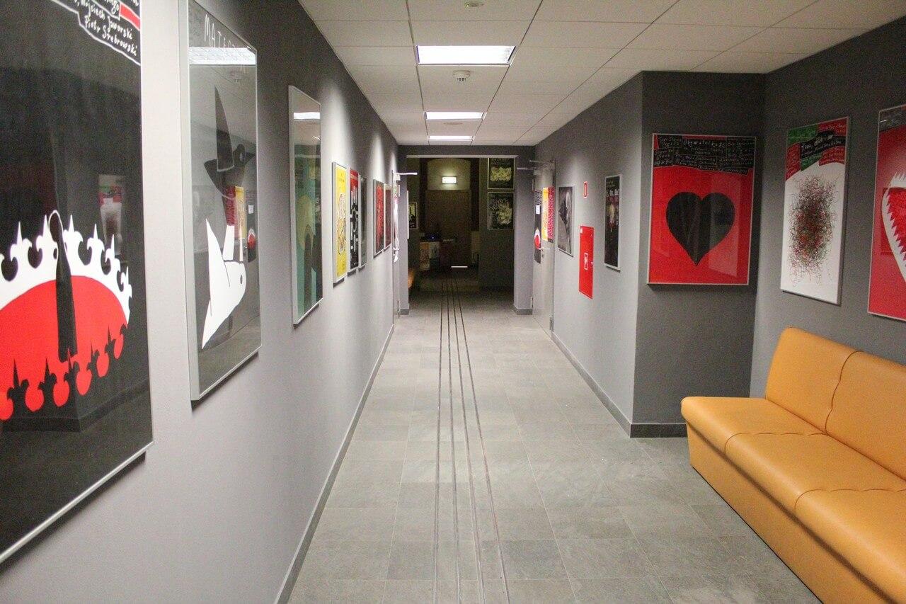 Wejście do teatru. Czary długi korytarz i ramy z plakatami na ścianach. Po prawo zółta kanapa.