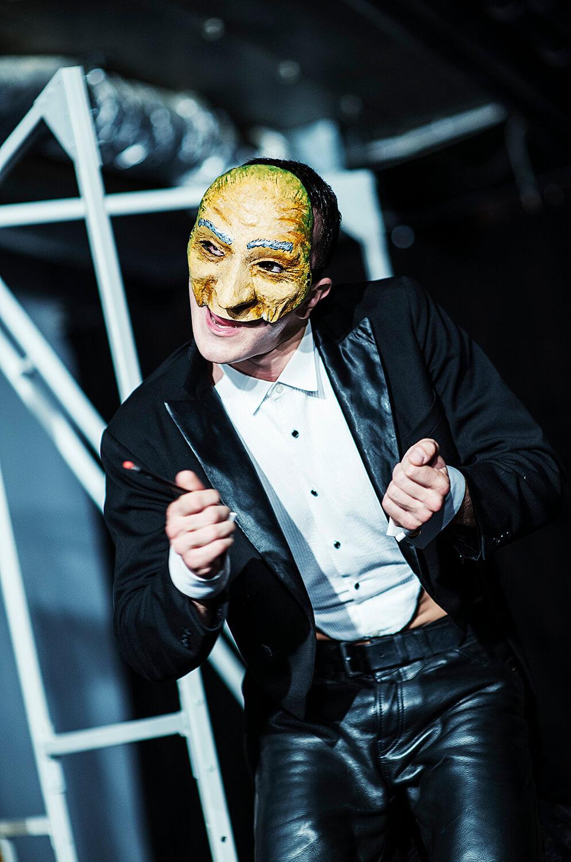 Zdjęcie ze spektaklu Pan Kot. Przedsawia aktora w e fraku, bez koszuli z maską w stylu komedii de larte na twarzy.