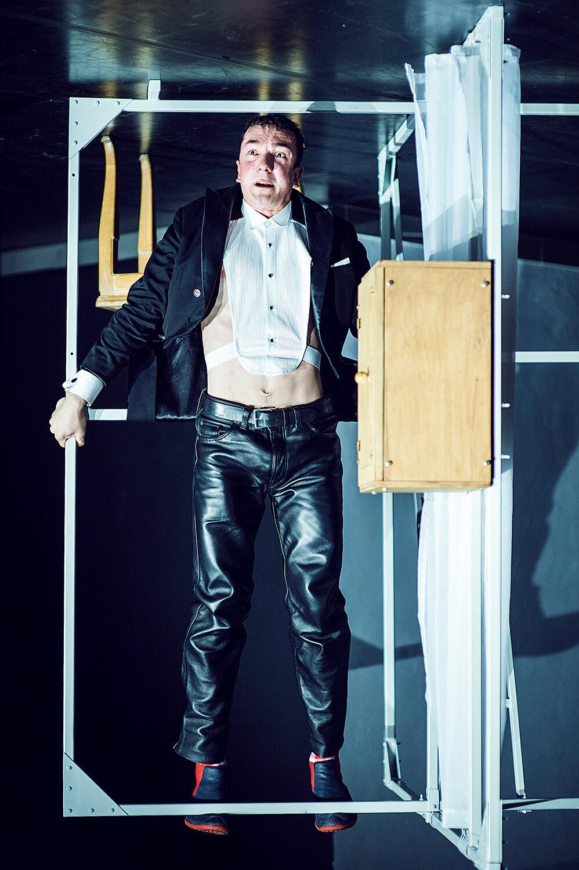 Zdjęcie ze spektaklu Pan Kot. Przedsatwia aktora we fraku, wiszącego do góry nogami na poręczy. Zdjęcie jest odwrócone.