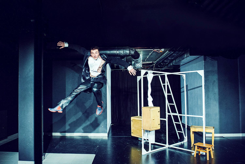 Zdjęcie ze spektaklu Pan Kot. Przedsatwia aktora we fraku skaczącego wysoko do góry.