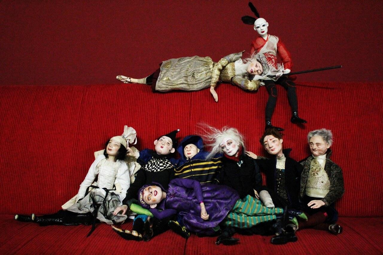 Zdjęcie do spektaklu spiąca Królewna. Pokazuje wszsytkie lalki wystepujące w spektaklu siedzące na czerwonej kanapie.