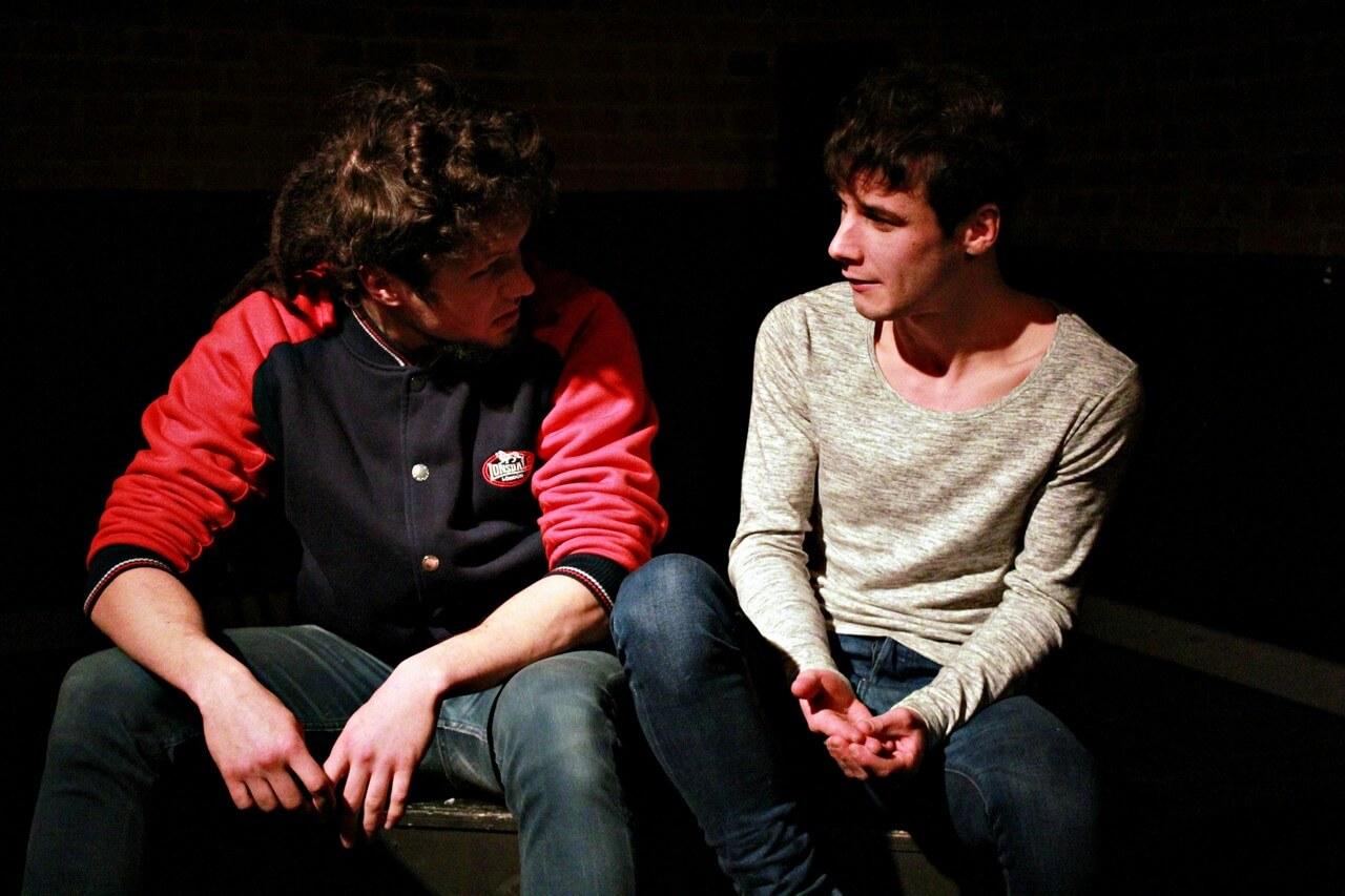Na zdjęciu dwóch młodych aktórów, ubranych na sportowo. Siedza na ławce i rozmawiają