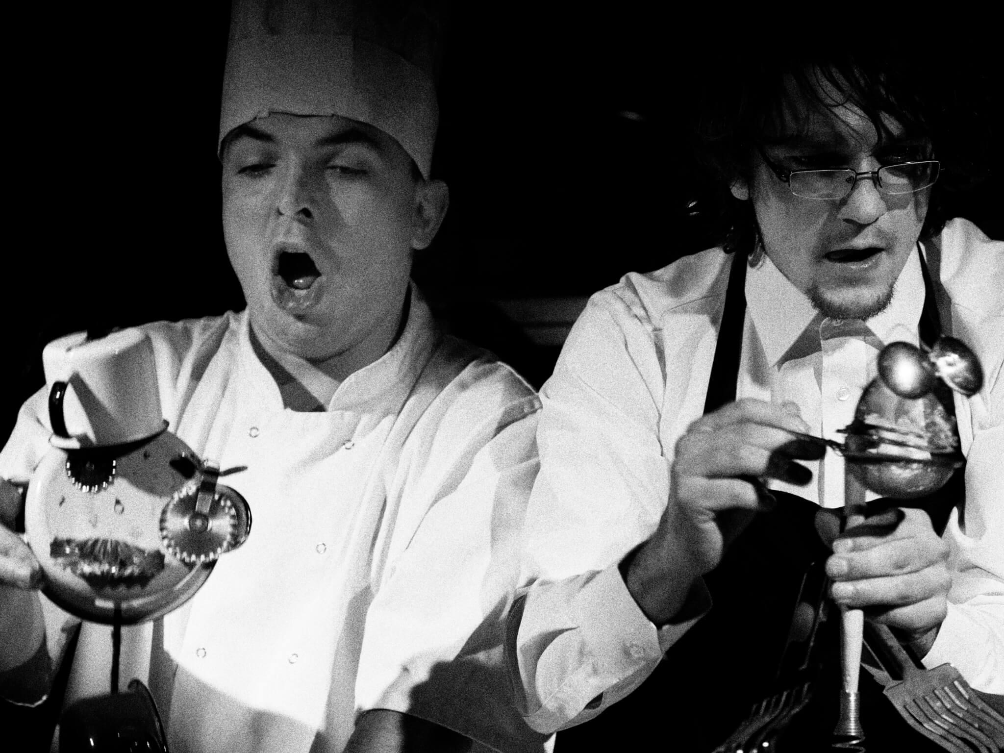 Zdjęcie ze spektaklu Wielkie Ciasto. Przedstawia dwóch aktorów przebranych za kucharzy animujących lalki zrobione z garnków.