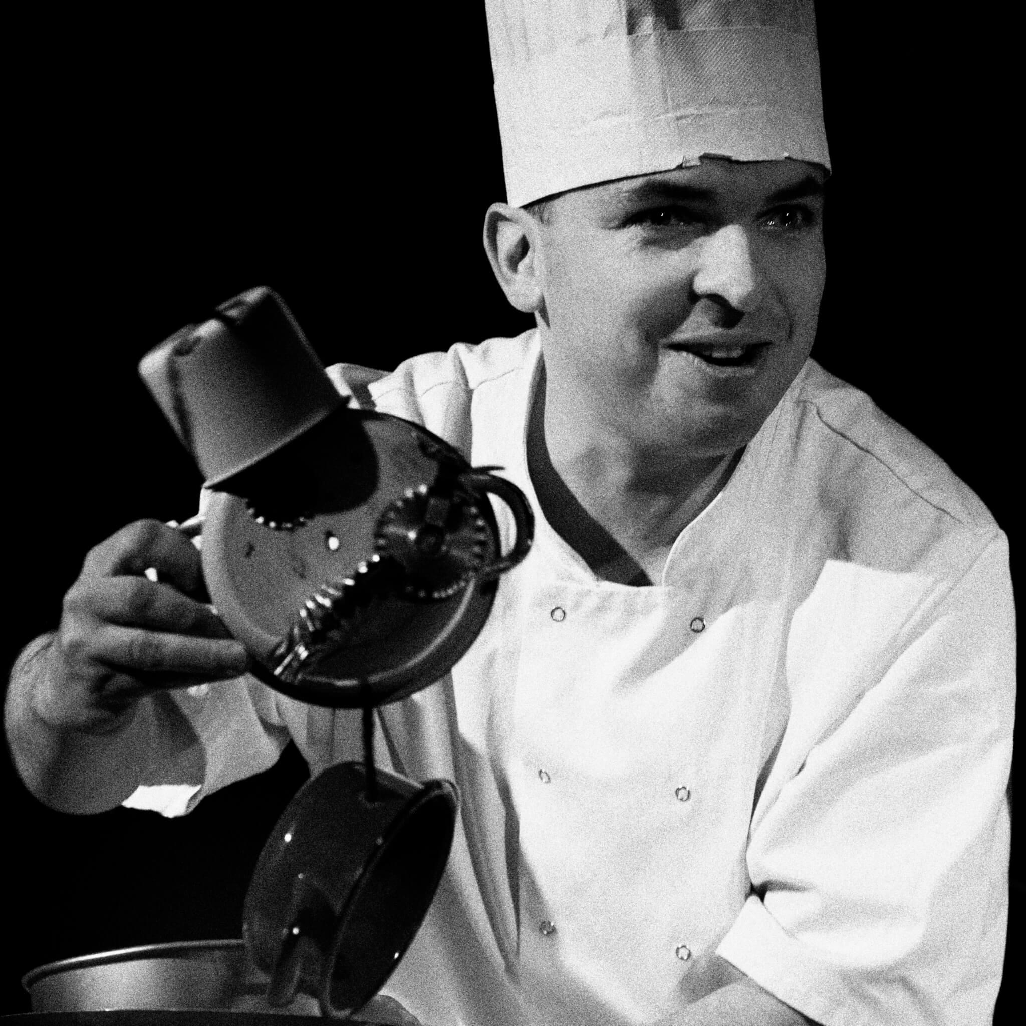 Zdjęcie ze spektaklu Wielkie Ciasto. Przedstawia aktora przebranego za kucharza animującego lalkę zrobiona z garnków.