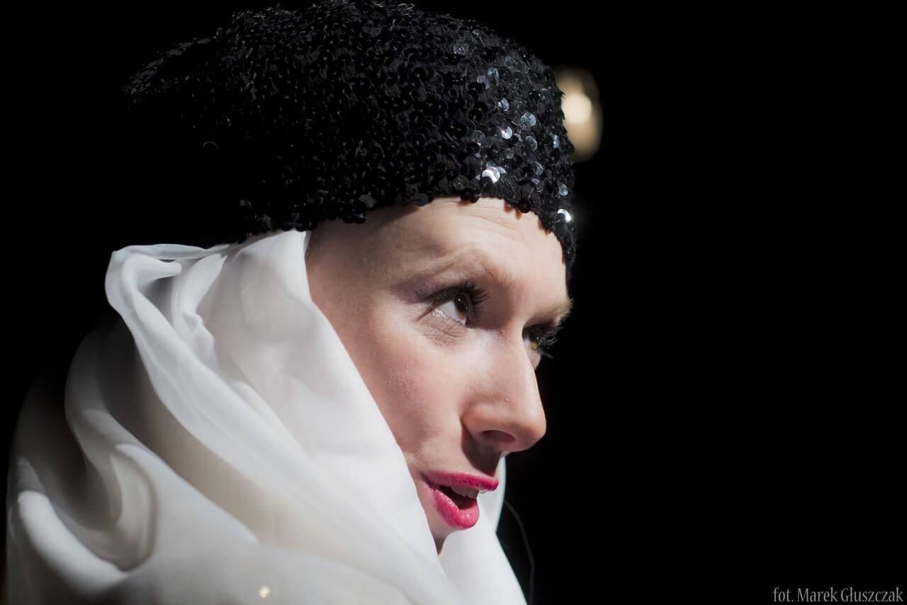 Zdjęcie ze spektaklu Burmistrz. Ukazuje młodą aktorkę w duzym zbliżeniu. Na głowie ma czarną czapke a twarz i szyję owinieta białą chustą.