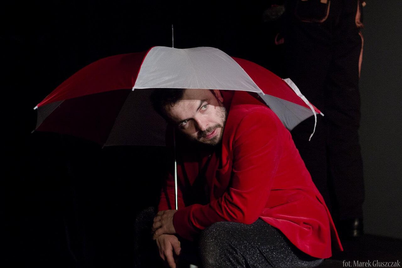 Zdjęcie ze spektaklu Burmistrz. Pokazuje mężczyzne w czerwonej marynarce schowanego pod biało- czerwonym parasolem.