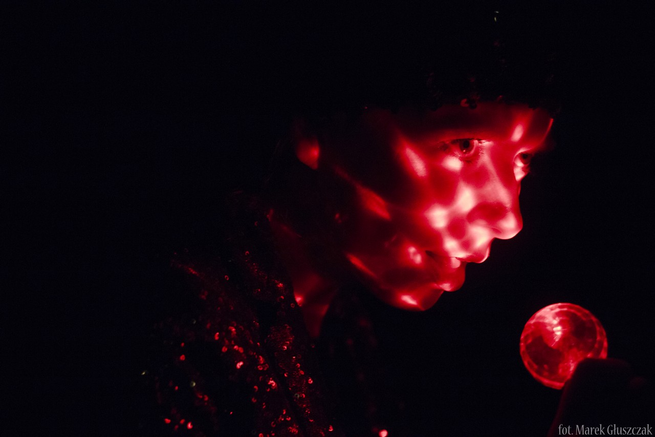 Zdjęcie ze spektaklu Burmistrz. Pokazuje twarz aktorki oświetlona czerwonym światłem.