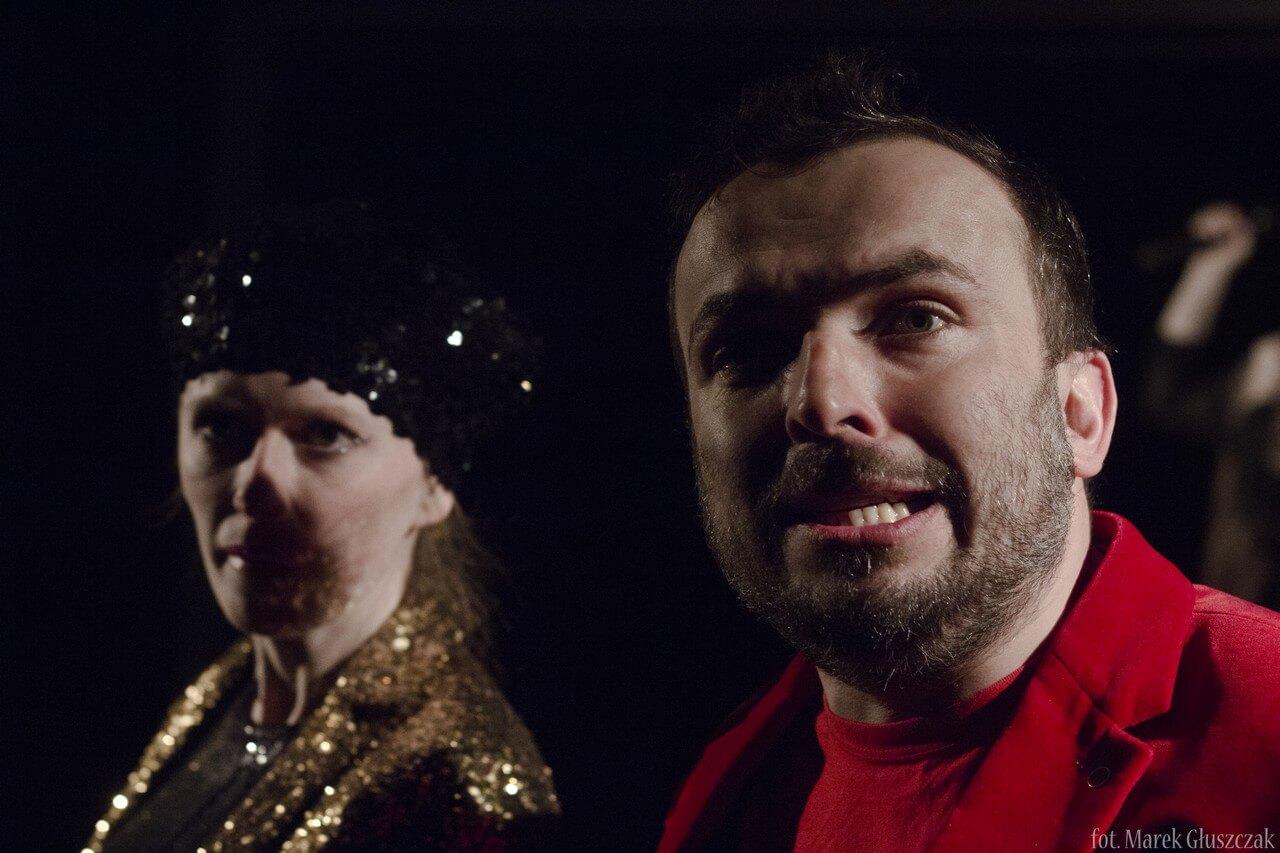 Zdjęcie ze spektaklu Burmistrz. W pierwszym planie aktor na duzym zbliżeniu, ubrany w czerwoną marynarke. W drugim planie aktorka w złotym żakiecie.