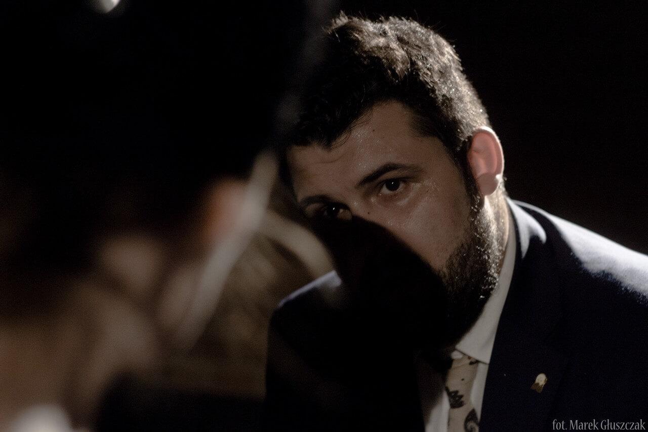 Zdjęcie ze spektaklu Burmistrz. Aktor w duzym zbliżeniu na którego twarz rzuca cień aktorka.