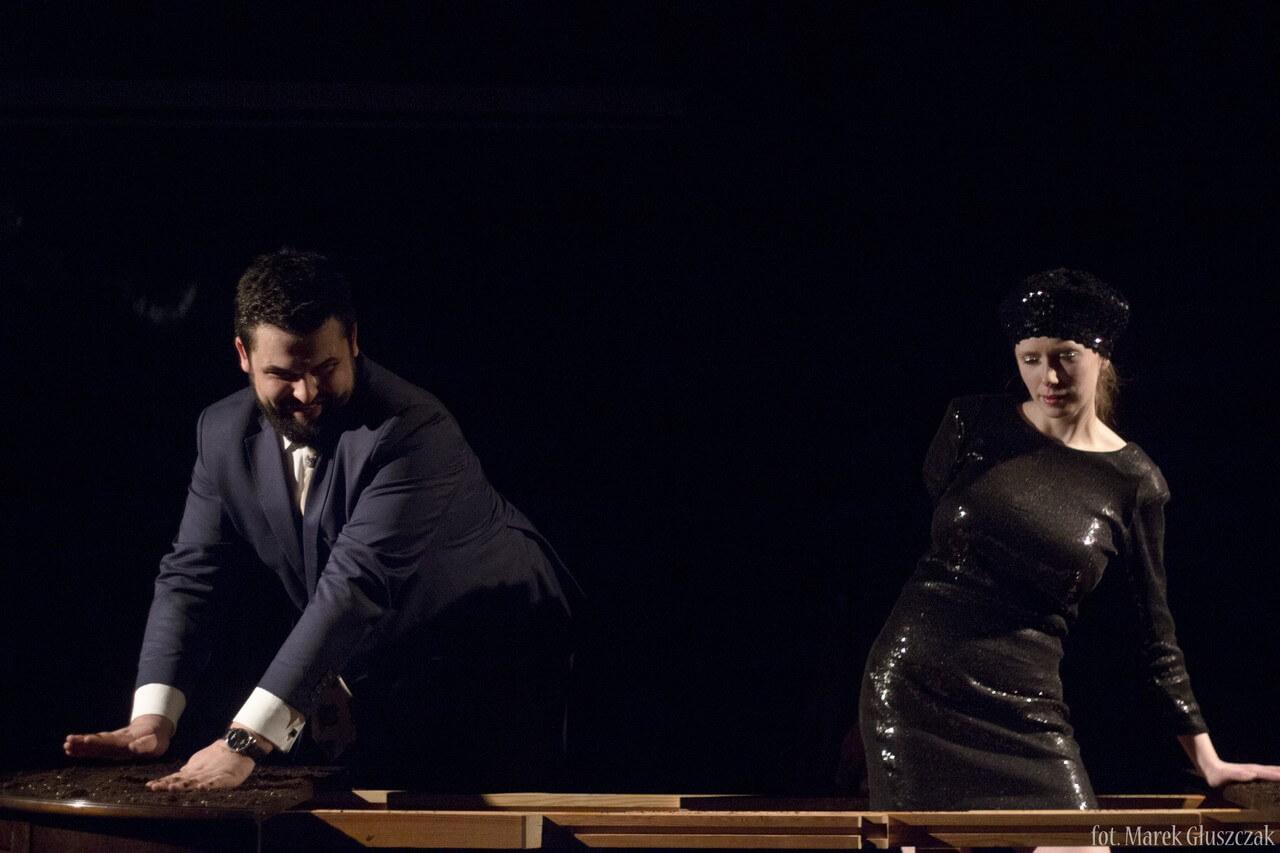 Zdjęcie ze spektaklu Burmistrz. Pokazuje dwoje aktorów przy stole. aktor w granatowym garniturze po lewo, aktorka w czarnej, ślniącej sukience po prawo.