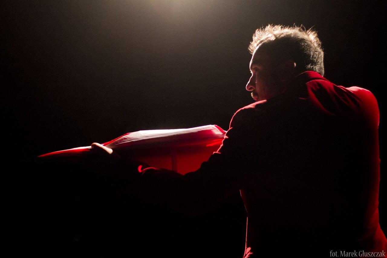 Zdjęcie ze spektaklu Burmistrz. Aktor trzyma parasolke i mierzy z niej jak z karabinu.