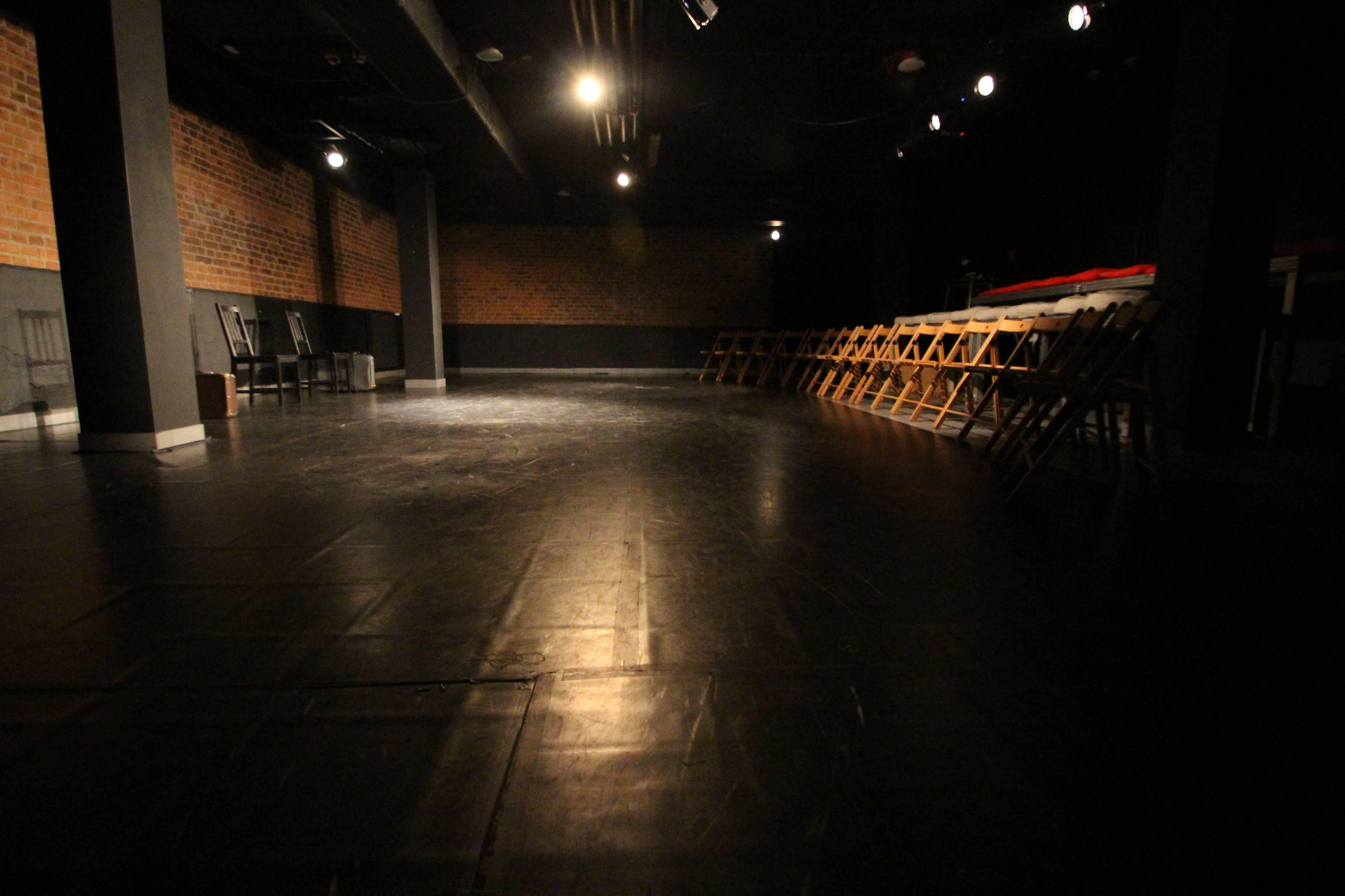 Zdjęcie sceny i widowni. czarna podłoga i drewniane kaszełka po prawo.