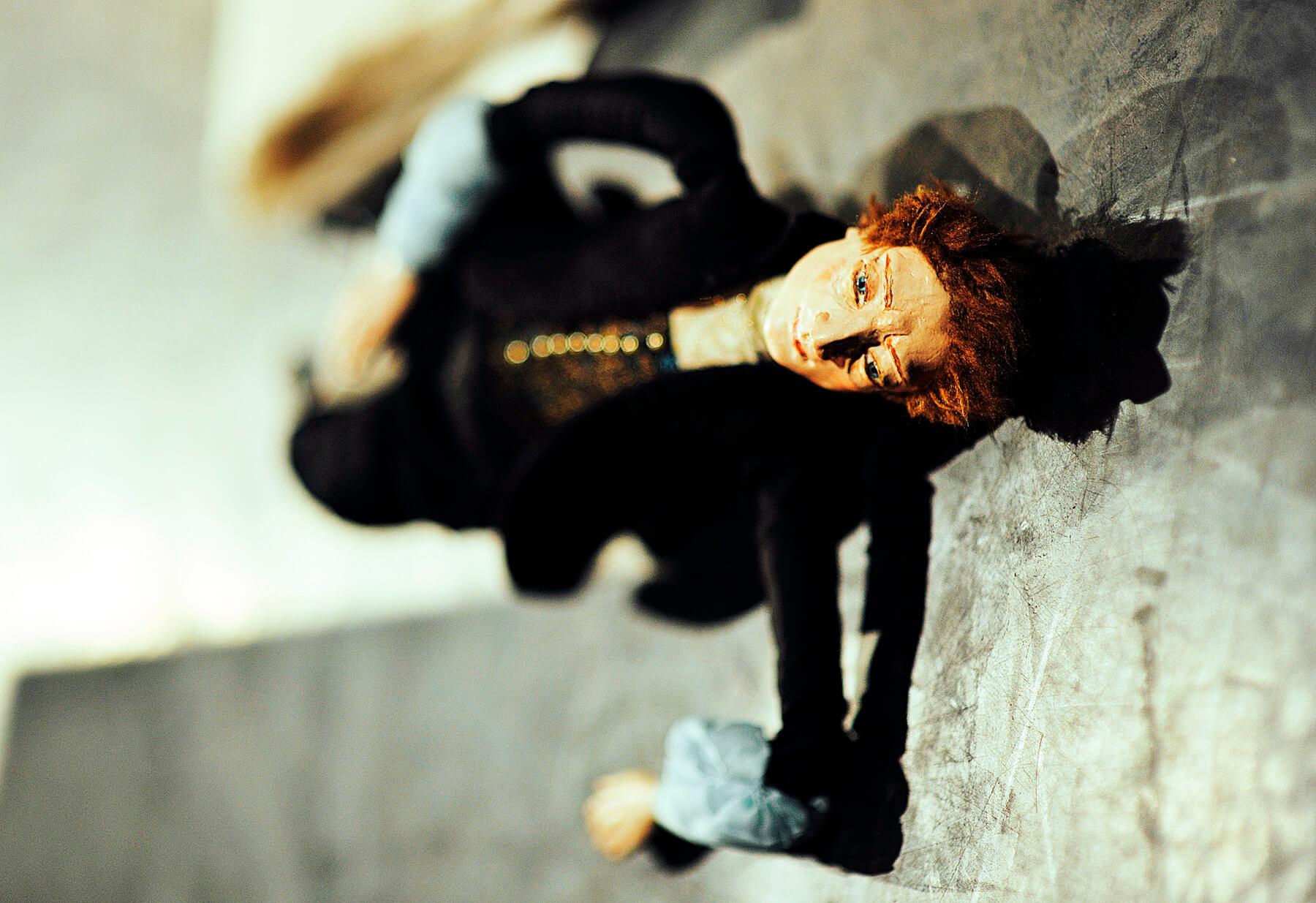 Zdjęcie ze spektaklu Śpiąca Królewna. Przedstawia lalkę księcia leżącą na stole.
