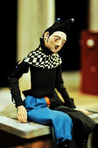 Zdjęcie ze spektaklu spiąca królewna. Przedstawia lalkę. Siedzącego błazna.