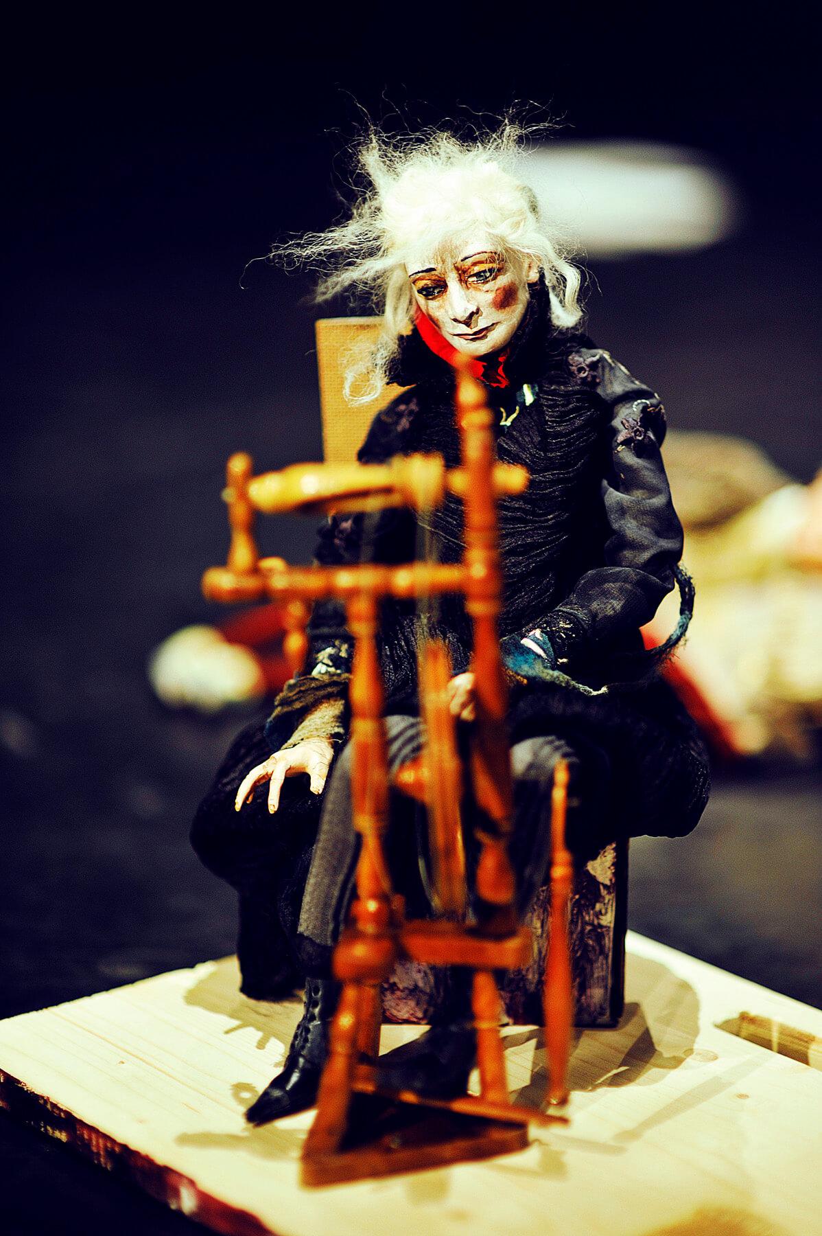 Zdjęcie do spektaklu spiąca Królewna. Pokazuje lalkę czarownicy siedzącą przy kołowrotku.