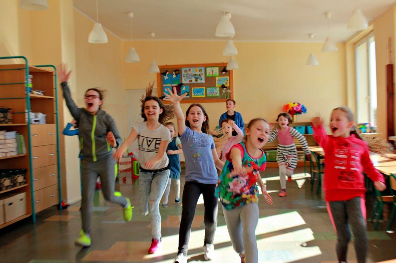 Na zdjęciu grupa dzieci w szkolnej klasie biegnących w stronę aparatu.