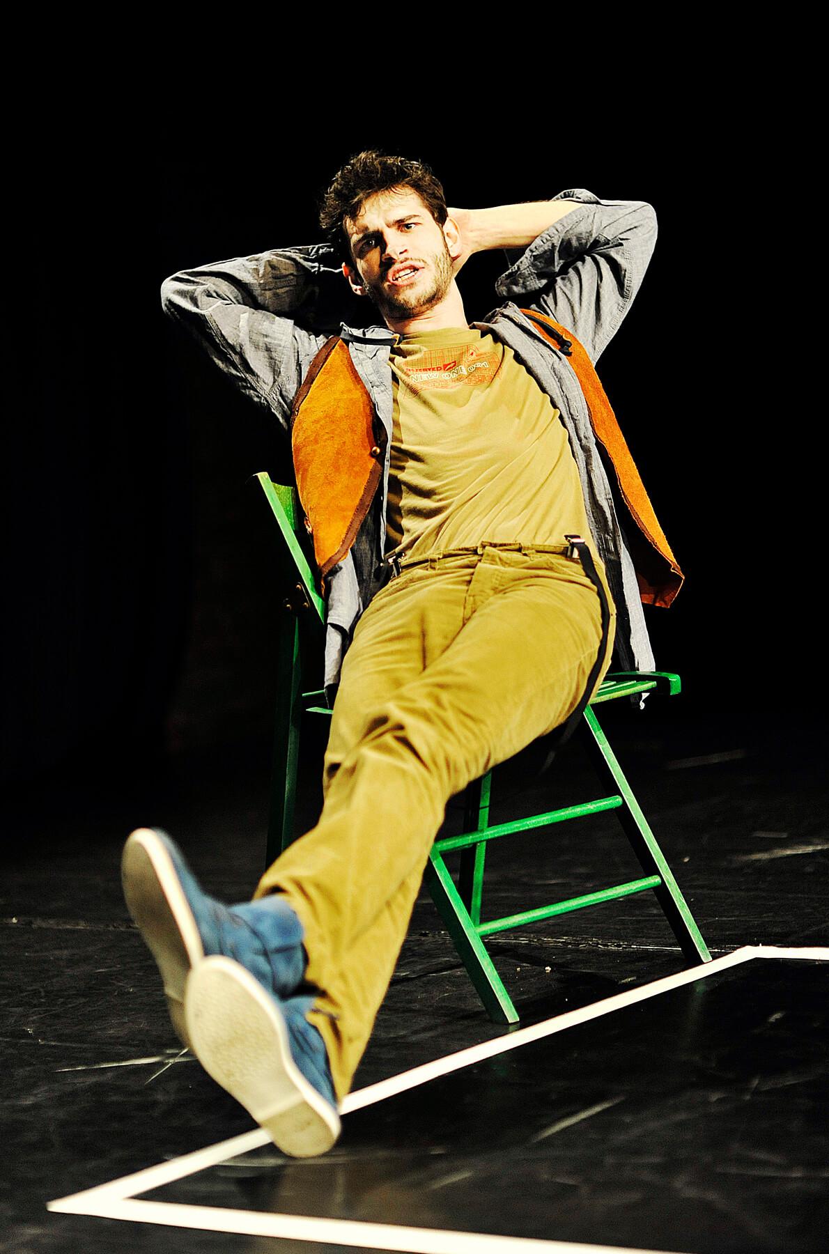 Zdjęcie do spektaklu Ścianananaświat. Aktor siedzi na zielonym krześle, z nogami wyciągnietym przed siebie i z rękami założonymi za głowę. Ubrany w niebieskie buty, zółte sztruksy, szara koszule i pomarańczową kamizelkę.