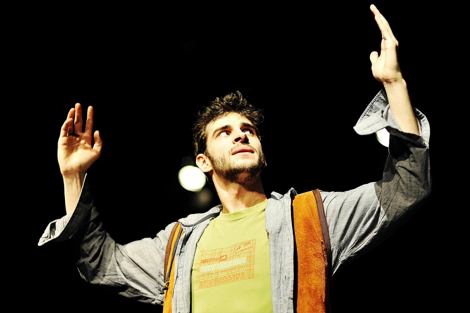 Zdjęcie do spektaklu Ścianananaświat. Aktor z uniesionymi rekoma, wzrok kieruje w prawa stronę.