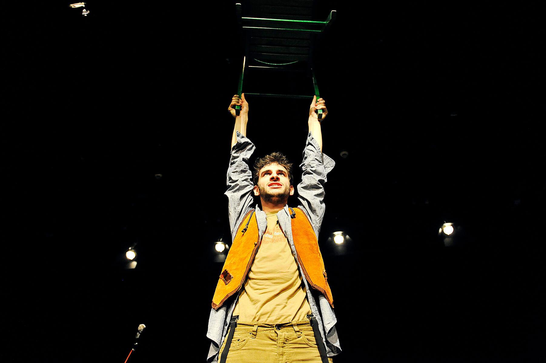 Zdjęcie do spektaklu Ścianananaświat. Aktor stoi z uniesionym w górze zielonym krzesłem.