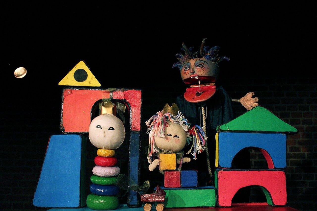 Zdjęcie do spektaklu Braciszek i siostrzyczka. Zamek zbudowany z dyzych kolorowych klocków. Król i królowa jako lalki z klocków i z duzymi okragłymi głowami. Z tyłu czarownica z szeroko otwartymi ustami.