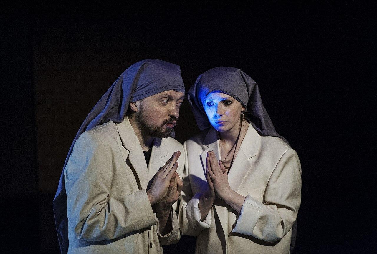 Zdjecie do spektaklu Von Bingen. Dwoje aktorów z kornetami na głowie i w białych marynarkach. mają złożone ręce jak do modlitwy.