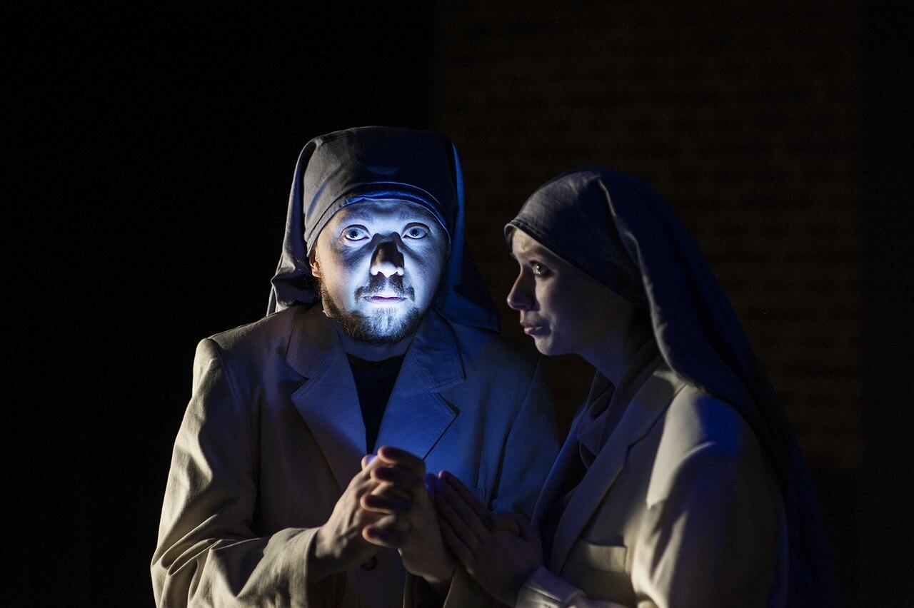 Zdjecie do spektaklu Von Bingen. Dwoje aktorów przebranych za zakonnice. Aktor ma rozsietloną twarz.