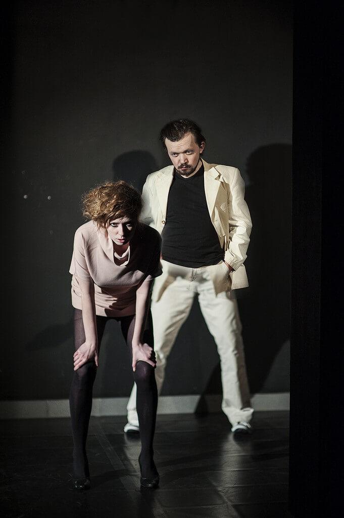 Zdjecie do spektaklu Von Bingen. Aktorka z różowej sukience stoi pochylona do przodu. Po prawo trochę za nia aktor w białym garniturze.