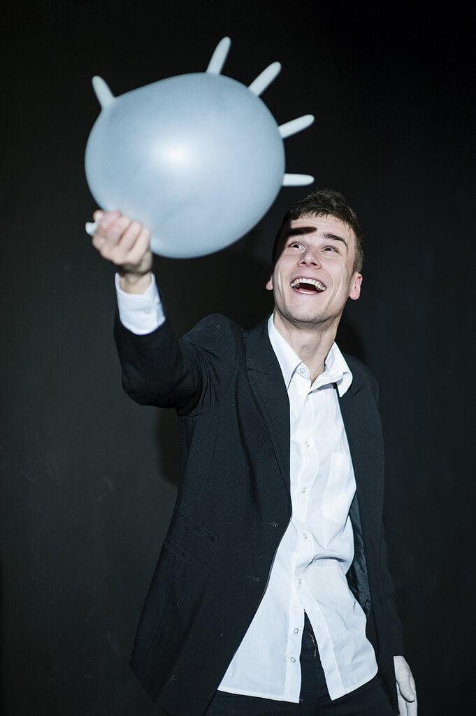 Zdjecie do spektaklu Von Bingen. Aktor w czarnym garniturze, trzyma balon z nadmuchanej lateksowej rekawiczki.