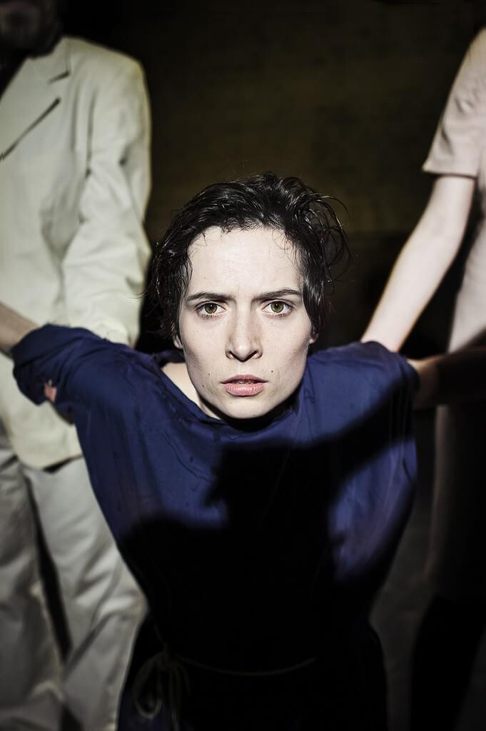Zdjecie do spektaklu Von Bingen. Aktorka z wygietymi do tyłu rekami, trezymana przez dwójkę aktorów.