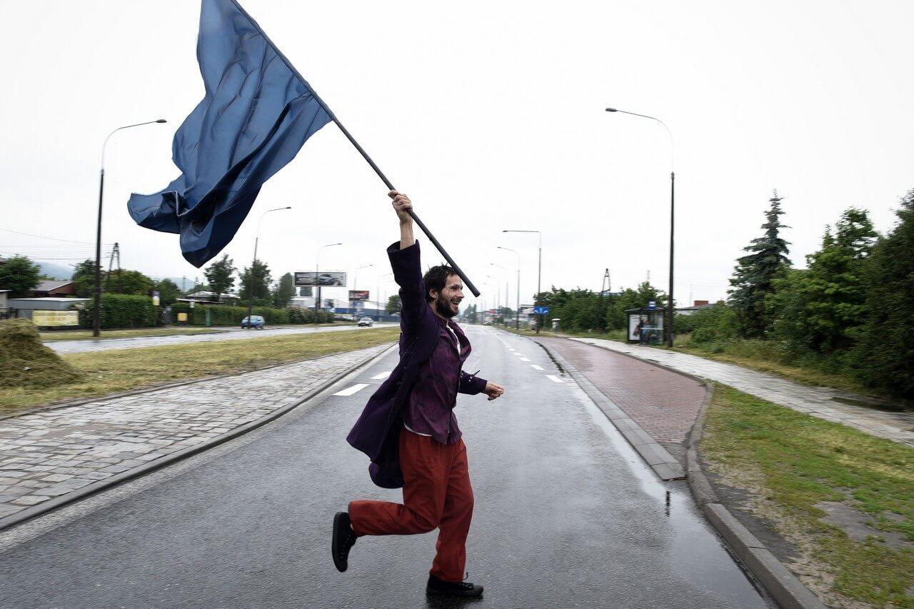 Aktor z dużą niebieską flaga przebiega przez ulicę.