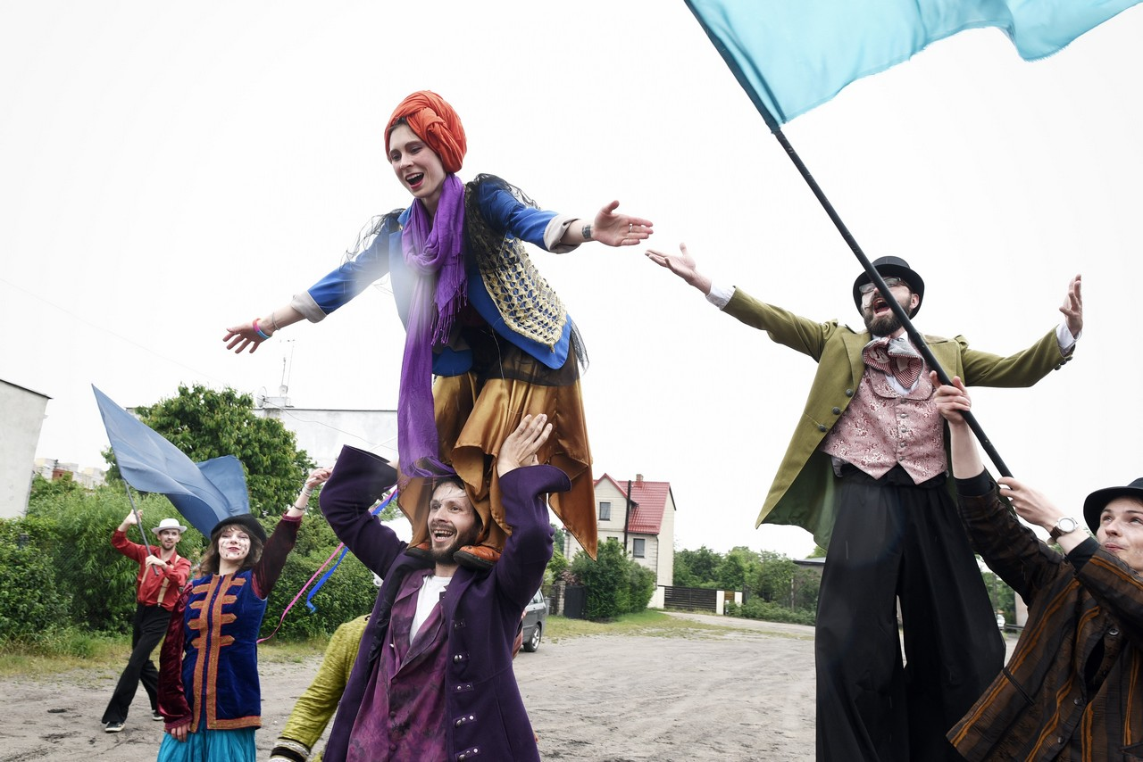 Aktorka stoi na ramionach aktora. Kolorowo przebrani. Widac też aktora na szczudłach i kolejnego wymachującego flagą.