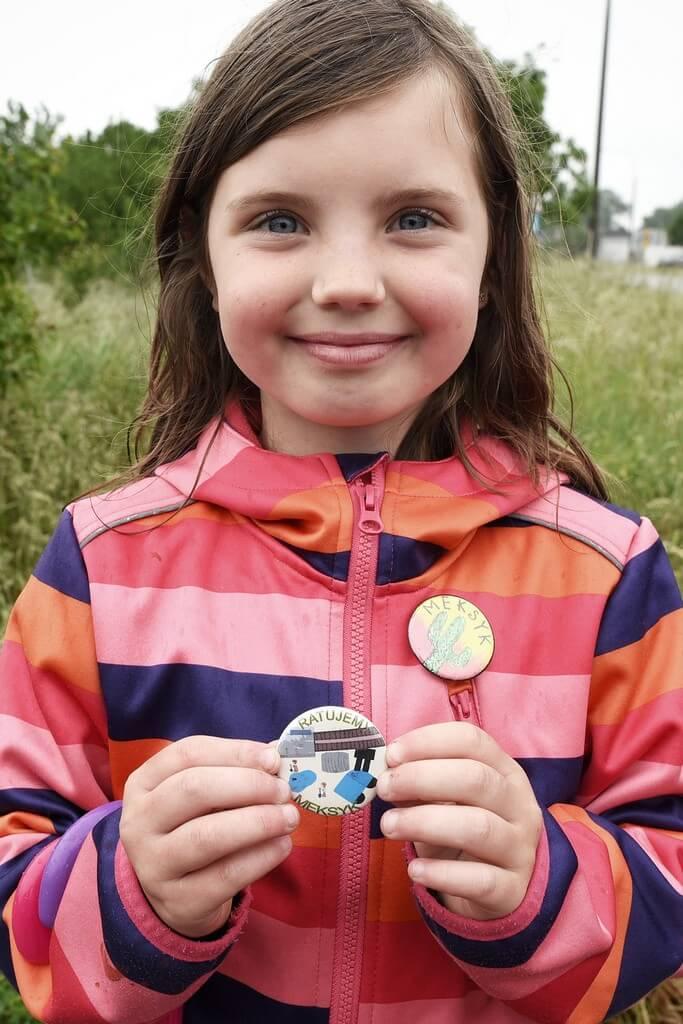 dziewczynka, w kurtce w paski prezentuje okragła przypinke z logiem swojej dzielnicy.